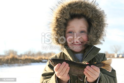 istock child ice fishing holding up his fish 182666861