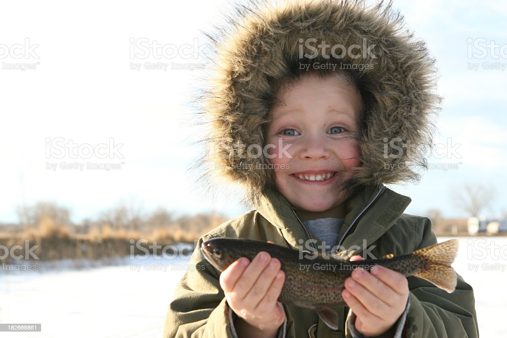 child ice fishing holding up his fish stock photo
