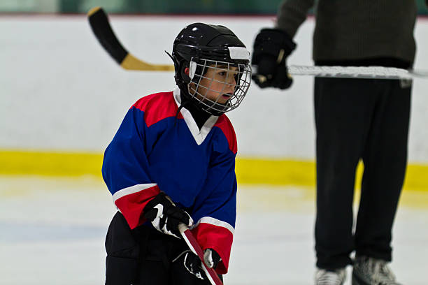 Child ice hockey player at practice with coach watching on stock photo