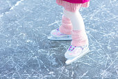 Child ice skating on frozen river. Kids skate. Close up of children leg and foot, knitted legwarmer. Active little girl having fun on ice rink. Healthy outdoor activity by cold winter weather.