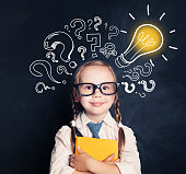 istock Child ideas. Smiling child school student with yellow book, lightbulb and chalk question marks. Brainstorm, problem and solution 1019219970