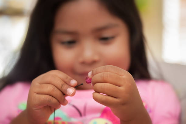 A child improving fine motor skills by using a pincer grip while holding string and beads. A child improving fine motor skills by using a pincer grip while holding string and beads. threading stock pictures, royalty-free photos & images