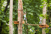 Boys in a helmets and safety equipment in adventure ropes park on the background of nature