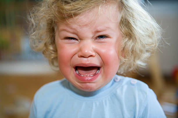 A child in a blue shirt that is crying stock photo
