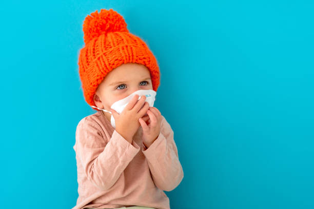 Child in a medical mask on a blue background stock photo