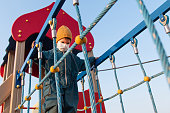 A boy in a protective mask plays in the playground during the coronavirus and Covid pandemic - 19