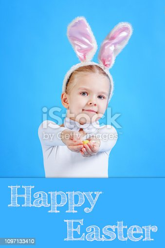 155096501 istock photo A child in a rabbit costume. Little girl holding an Easter egg. Cute Bunny, a symbol of the holiday. The inscription Happy Easter. Bright photo on a blue background. 1097133410