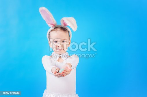 155096501 istock photo A child in a rabbit costume on a bright blue background Little girl holding an Easter egg. Cute bunny, holiday symbol. Copy space. Bright photo with space for text. 1097133446