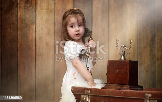 A child in a retro interior and an old phone sits on the floor. A small child a traveler in vintage decorations. Child traveler is calling by phone.
