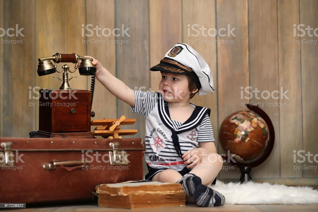 A child in a retro interior and an old phone sits on the floor. stock photo