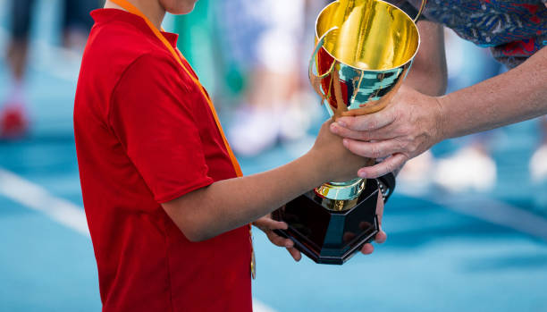 Child in a sportswear receiving a golden cup. Young atlete winning the sports school competition. Boy with golden medal getting an award for the best player of the tournament stock photo