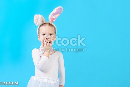 155096501 istock photo A child in a white rabbit costume on a blue background. Cute little girl with ears of a hare, covers her mouth in surprise. Advertising photo with space for text. 1094649156