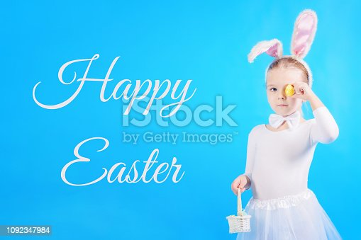 155096501 istock photo Child in a white rabbit costume. The little girl holds in one hand a basket and in the other hand an egg with which she covers the eye. Cute bunny, holiday symbol. Bright picture on a blue background, the inscription Happy Easter. 1092347984