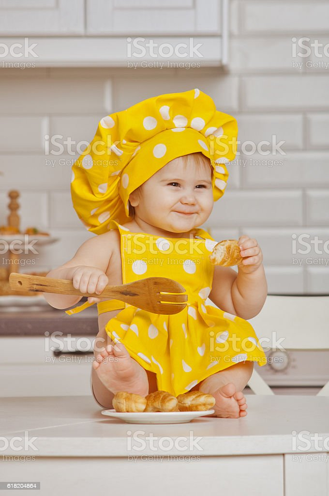 child in a yellow suit of the cook in white peas stock photo