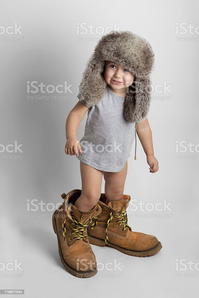 Child in adult's shoes and hat stock photo