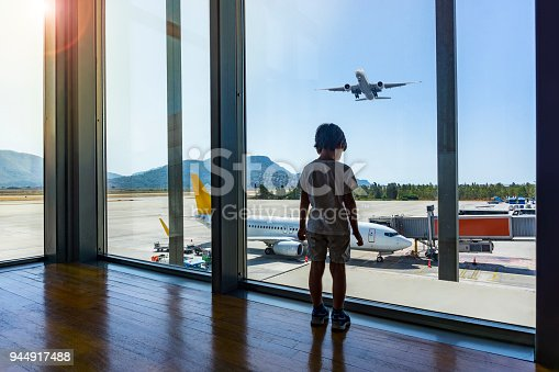In airport hall child looks at the plane through window. Dalaman airport, Turkey.