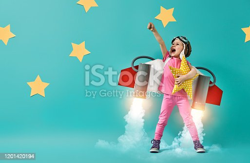 Little child in an astronaut costume is playing and dreaming of becoming a spaceman. Portrait of funny kid on a background of bright blue wall.