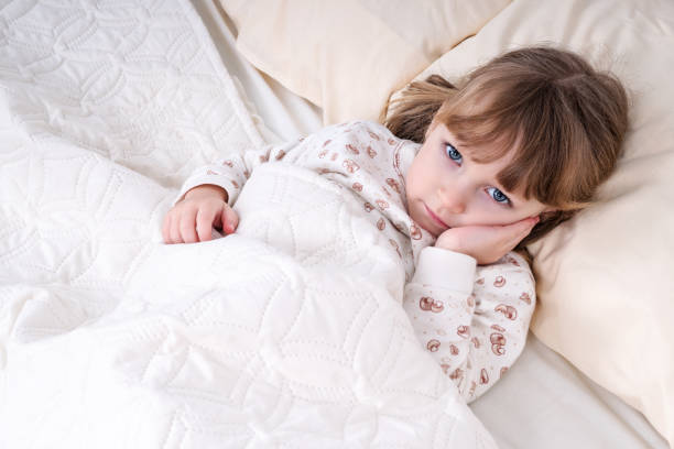 Child in bed with hand on cheek Little beautiful girl lying in bed and holding her cheek with a sick tooth toothache stock pictures, royalty-free photos & images