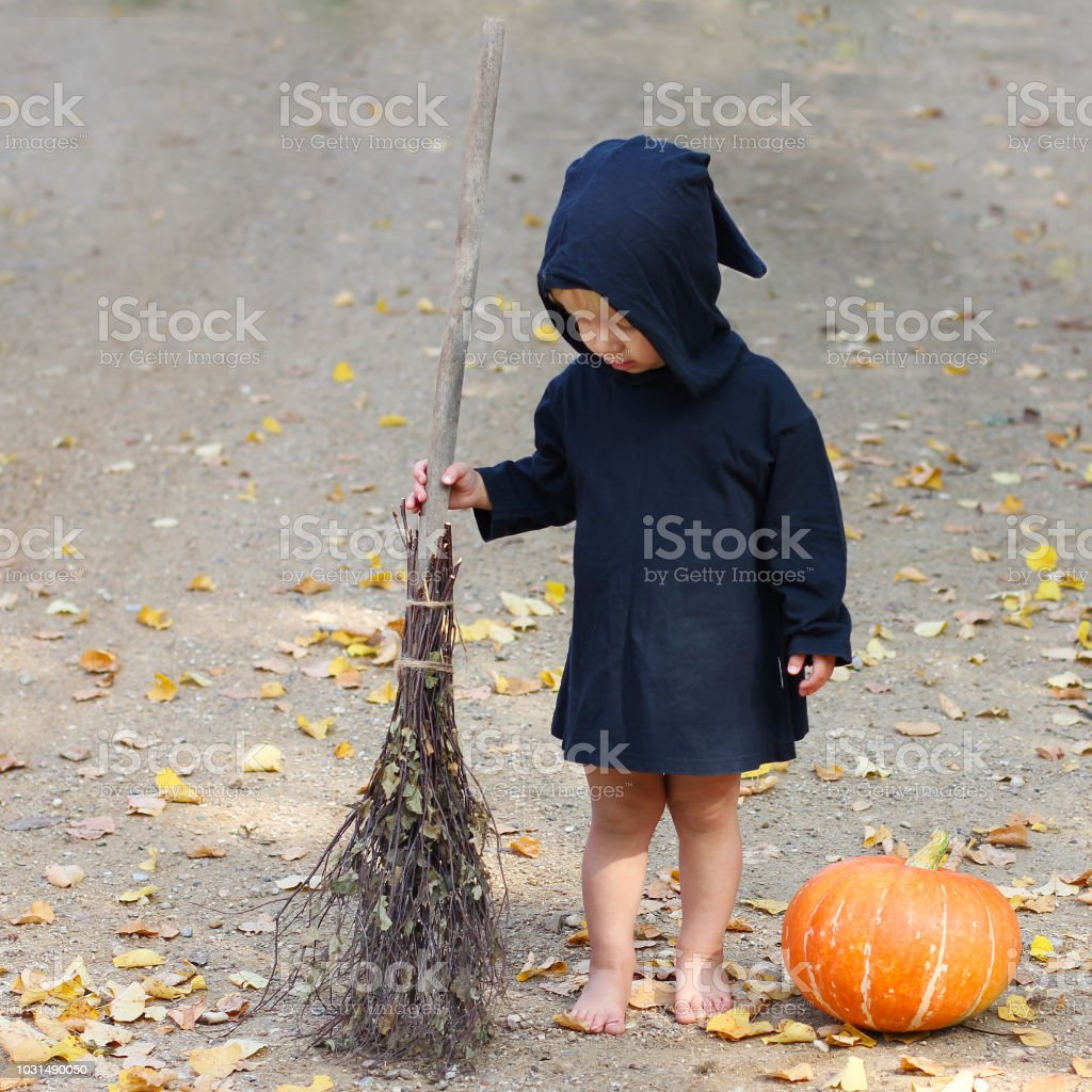 child in black sorcerer or witch suit stands with broom near fresh pumpkin, square frame stock photo