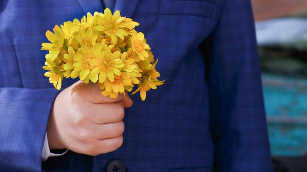 kind in blaue jacke mit gelben bouquet. - hochzeitsspiele eltern stock-fotos und bilder