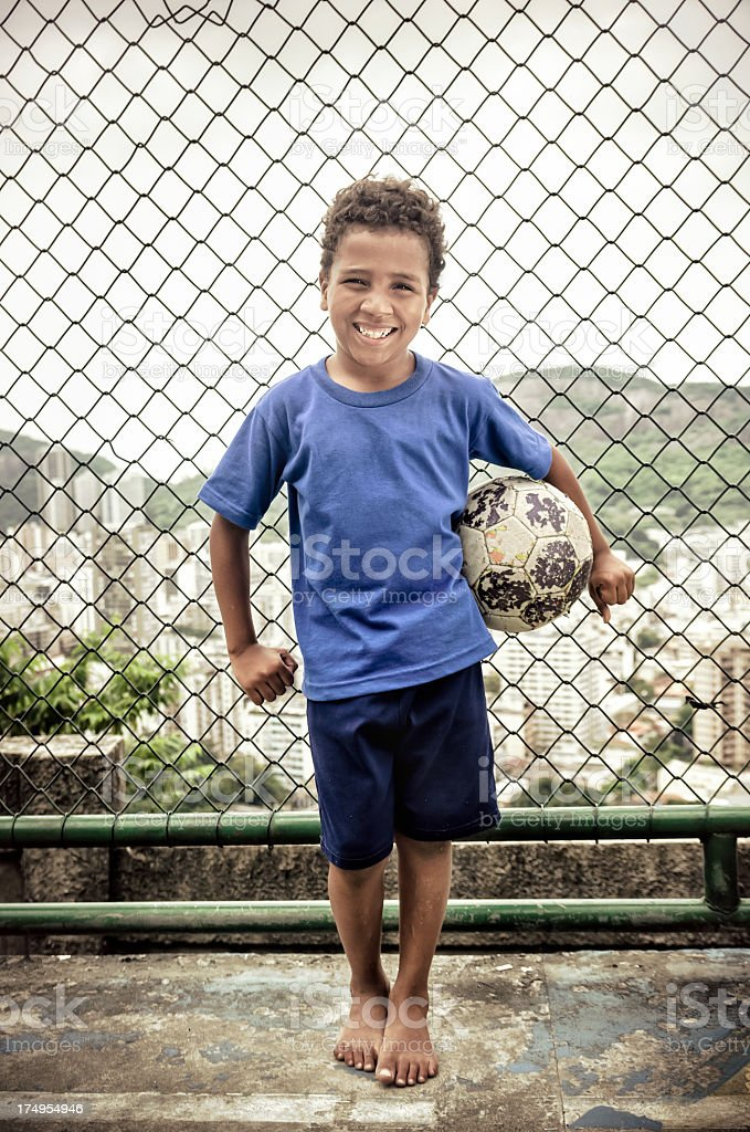 Child in blue shirt holding soccer ball stock photo
