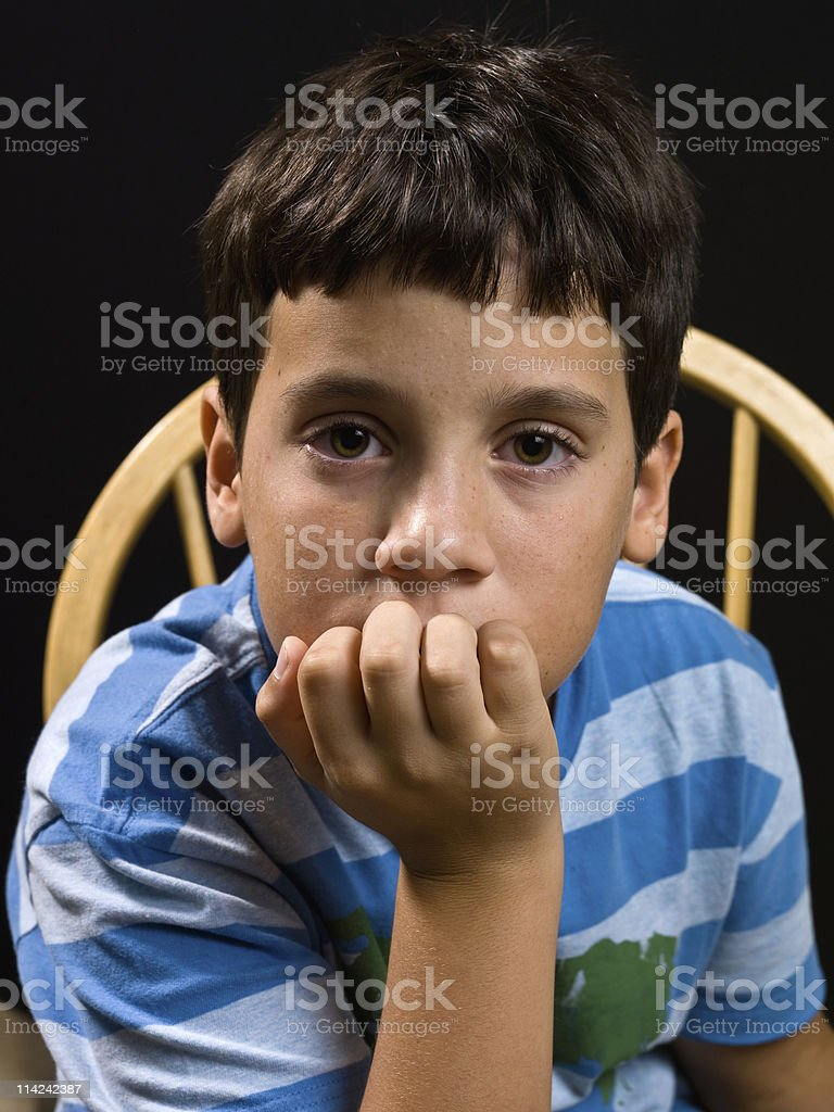 Child in blue stripy shirt sitting on wooden chair royalty-free stock photo
