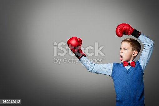 istock Child in Boxing Gloves, Elegant Kid Boy Boxer Raised Arms Up, Gray Background 960512512