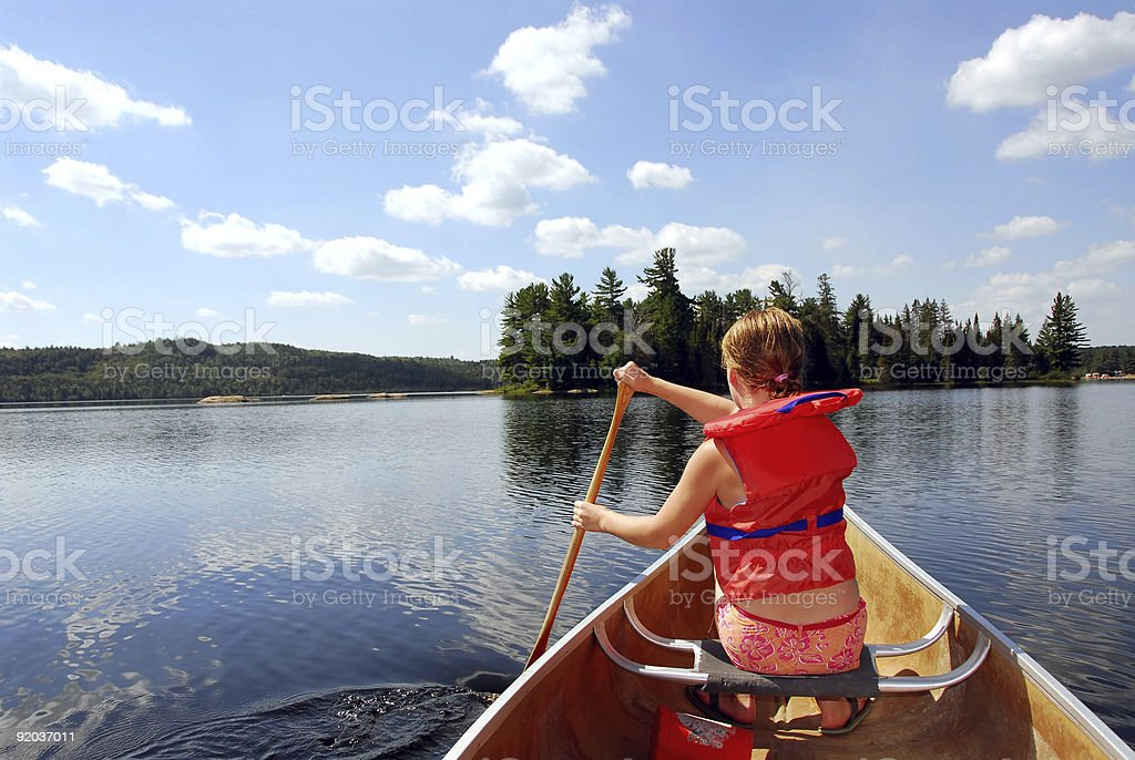Child in canoe Young girl in canoe paddling on a scenic lake Adventure Stock Photo