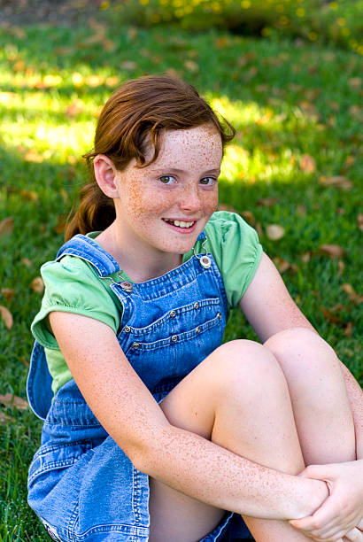 Child in Coveralls, Redhead and Freckles Girl Happy & Smiling Outdoors stock photo