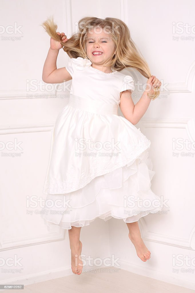 Child in dress jumping and holding her hair. White background stock photo