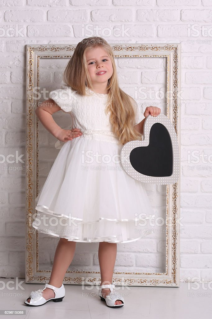 Child in dress with heart and frame. Close up. White stock photo