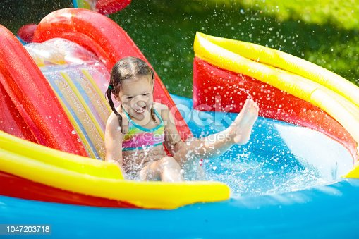 istock Child in garden swimming pool with slide 1047203718