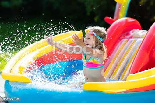 istock Child in garden swimming pool with slide 973727106