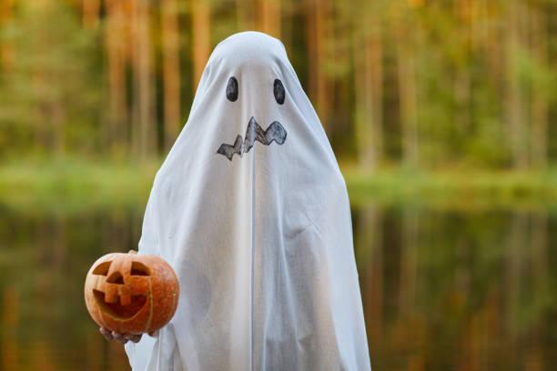 kind im geisterkostüm an halloween - geist kostüm stock-fotos und bilder