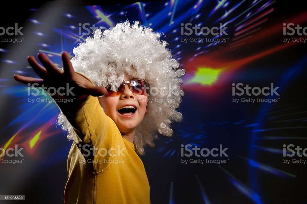 Child in glasses and a wig dances in disco lights stock photo