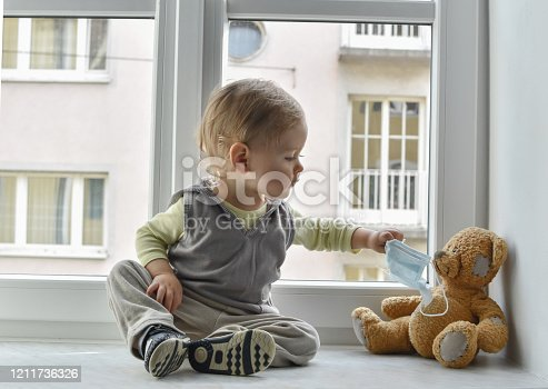 Child in home quarantine at the window putting a medical mask on his sick teddy bear, for protection against viruses during coronavirus COVID-19 and flu outbreak. Children and illness disease concept