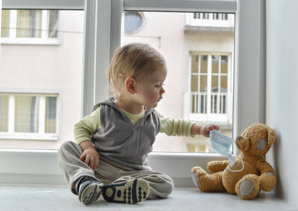 Child in home quarantine at the window putting a medical mask on his sick teddy bear, for protection against viruses during coronavirus COVID-19 and flu outbreak. Children and illness disease concept Child in home quarantine at the window putting a medical mask on his sick teddy bear, for protection against viruses during coronavirus COVID-19 and flu outbreak. Children and illness disease concept quarantine stock pictures, royalty-free photos & images