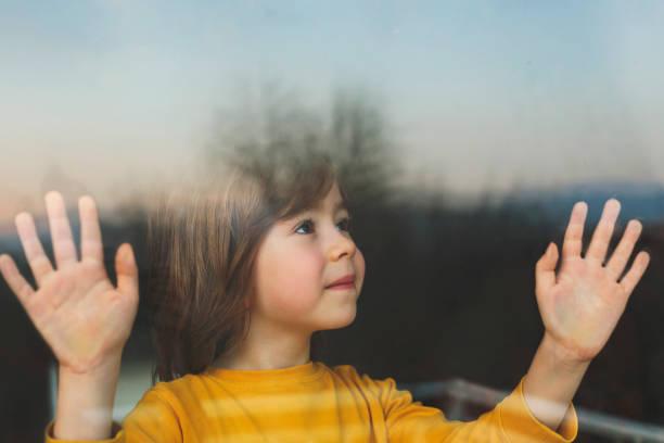 child in isolation at home - hand on glass covid foto e immagini stock