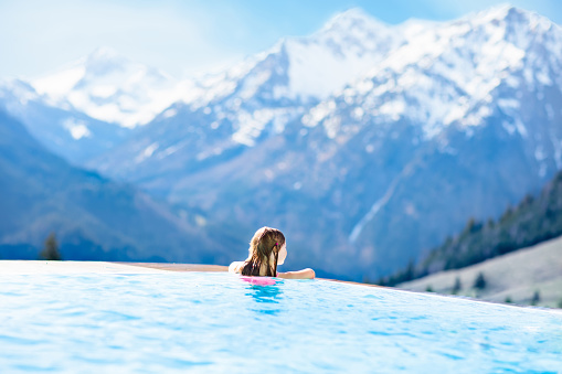 istock Child in outdoor swimming pool of alpine resort 1048494898