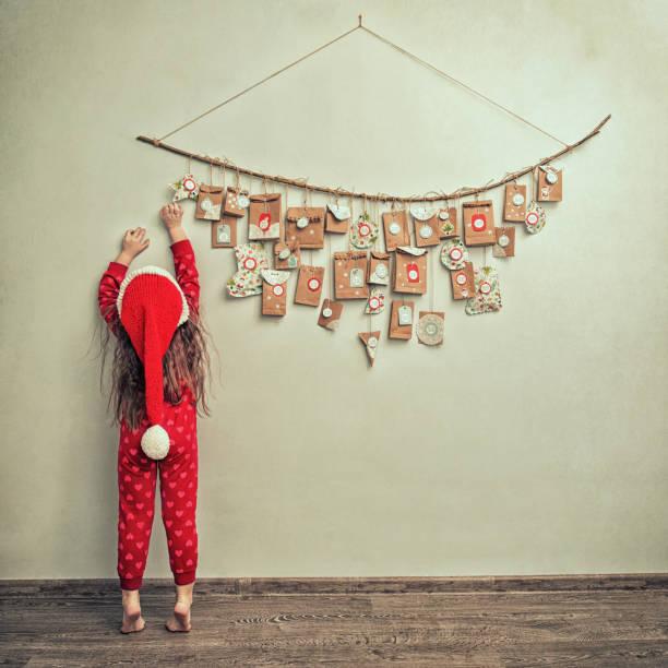 kind im schlafanzug und christmas cap erstreckt sich über adventskalender mit kleinen geschenken. kind zählt die tage bis silvester - weihnachtsessen ideen stock-fotos und bilder