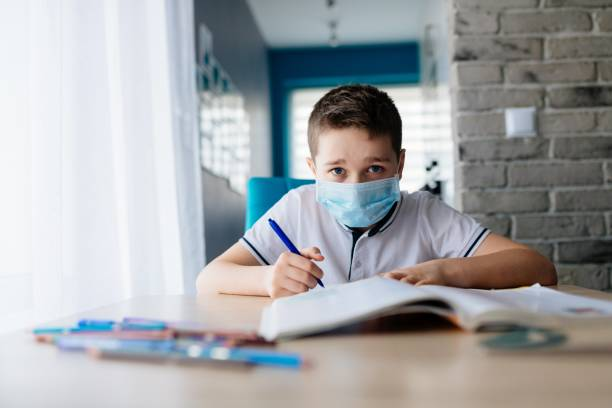 Child in protective medical mask doing his homework. School closed during coronavirus stock photo