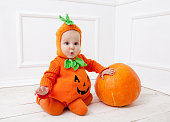 istock Child in pumpkin suit on white background with pumpkin 492082316