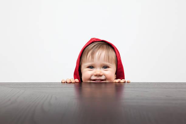 enfant jouant cache-cache - indiscret photos et images de collection