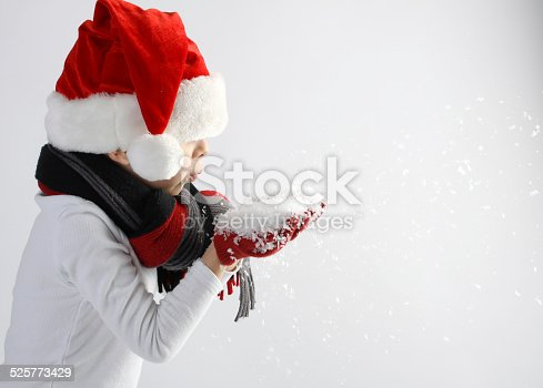 istock Child in santa claus hat blowing snowflakes 525773429