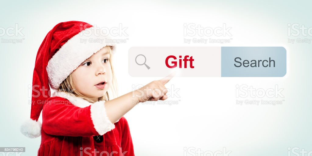 Child in Santa Hat look for a gift ing Gifts. Christmas Child stock photo