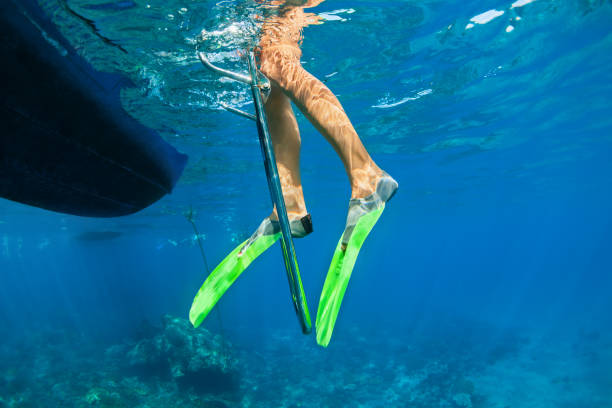 Child in snorkelling fins stand on divers boat ladder Child in snorkelling fins stand on divers boat ladder for diving underwater in tropical coral reef sea pool. Travel lifestyle, water sport outdoor adventure on family summer beach holiday with kids. diving flipper stock pictures, royalty-free photos & images