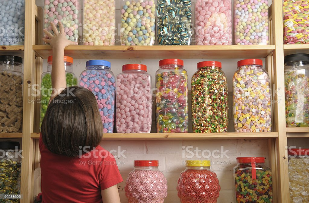 child in sweet shop stock photo