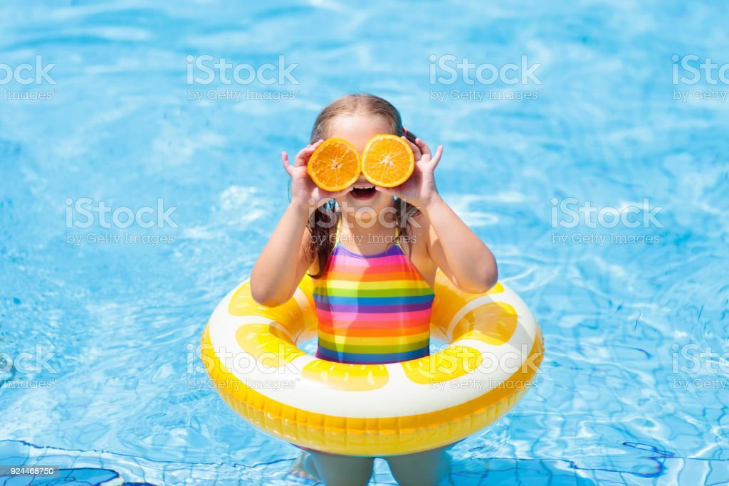 Child in swimming pool. Kid eating orange. stock photo
