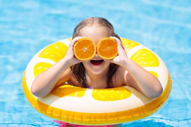 kind im schwimmbad. kinder essen orange. - sonnenbrille kleinkind stock-fotos und bilder