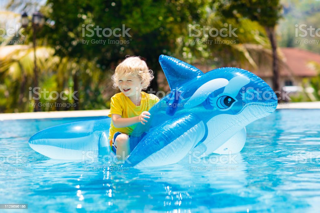 Child in swimming pool. Kid on inflatable float stock photo